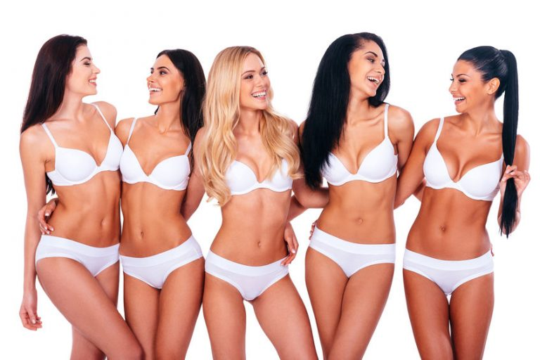 Carefree beauties. Group of cheerful women wondering does coolsculpting work? Wearing lingerie embracing and looking at each other while standing against white background