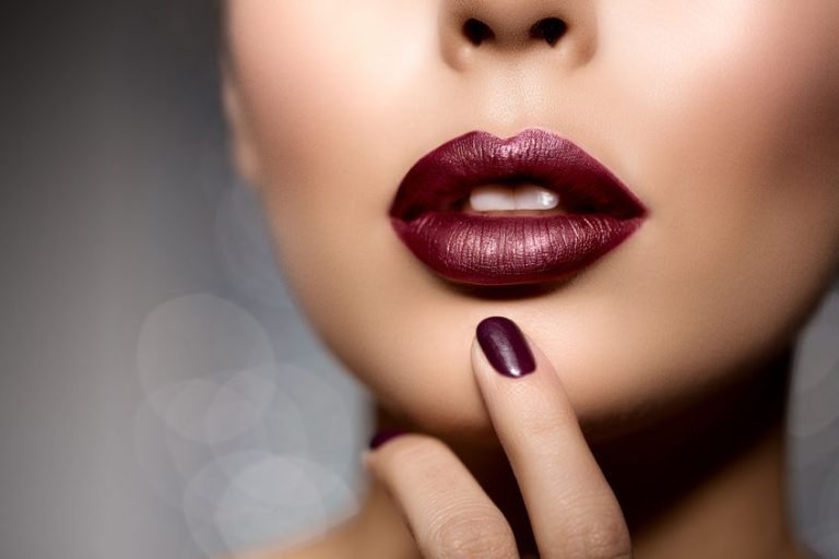 red woman lips close up. beautiful model girl with lipstick, manicure thinking about lip filler risks